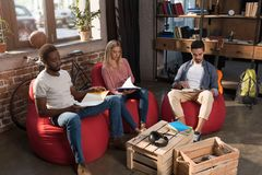 Multiethnic students studying together. Multiethnic students with books studying together at home Stock Photos