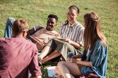Multiethnic students studying together. Cheerful young multiethnic students studying while sitting together on grass Stock Photo