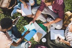 Multiethnic students studying together. Overhead view of multiethnic group of students studying together while sitting on grass Stock Photo
