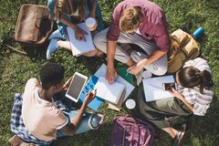 Multiethnic students studying together. Overhead view of young multiethnic students studying together while sitting on grass Stock Photo