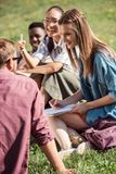 Multiethnic students studying together. Smiling young multiethnic students studying while sitting together on grass Stock Image
