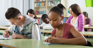 Multiethnic students studying together. Young multiethnic students studying together in the classroom Stock Images