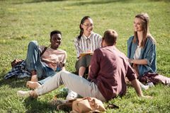Multiethnic students studying together. Young multiethnic group of students studying and smiling each other while sitting on grass Royalty Free Stock Photos