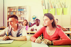 Multiethnic students studying together. Young positive multiethnic students studying together in the classroom Stock Photo