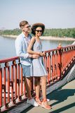 multiethnic stylish couple in sunglasses standing on bridge stock photo