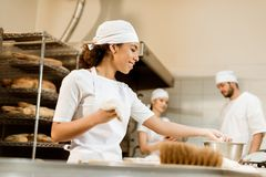 Multiethnic team of bakers working together. At baking manufacture royalty free stock images