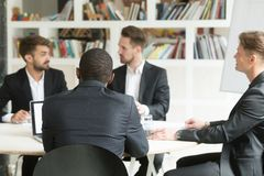 Multiethnic team of male coworkers discussing corporate plans du. Ring briefing. Businessmen having discussion about investment opportunities, new business Royalty Free Stock Images
