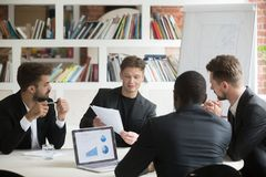 Multiethnic team of male coworkers discussing corporate plans du. Multiethnic team of male coworkers discussing financial plan during briefing. CEO consulting Stock Images