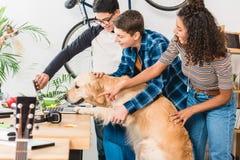 Multiethnic teenagers showing something on laptop. To dog royalty free stock photo