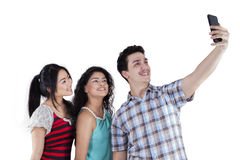 Multiethnic teenagers taking self photo. Joyful multiracial teenagers using a smartphone to take self picture in the studio, isolated on white Royalty Free Stock Photo