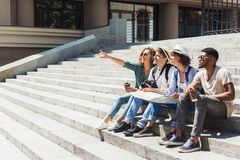 Multiethnic tourists sitting on stairs with map. And pointing to landmark, copy space royalty free stock photos
