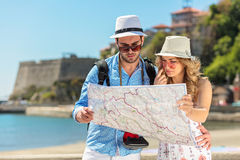 Multiethnic traveler couple using generic local map together on sunny day. stock photos