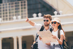 Multiethnic traveler couple using generic local map together on sunny day. Honeymoon trip, backpacker tourist, Asia tourism. Multiethnic traveler couple using Stock Photo