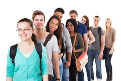 Multiethnic university students standing in a row. Portrait of multiethnic university students standing in a row isolated over white background Stock Photography