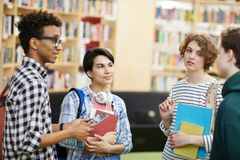 Multiethnic university students talking in library. Group of content pensive young multiethnic university students standing in modern library area and talking stock images