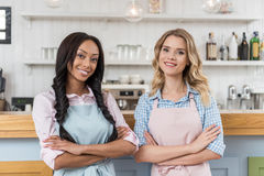 Multiethnic waitresses looking at camera while standing together with arms crossed at cafe Stock Image