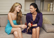 Multiethnic Women With Drinks Sitting On Couch. Two happy multiethnic young women with drinks sitting on couch Stock Image