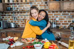 Multiethnic women hugging while cooking pizza together Stock Photos
