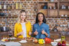 Multiethnic women showing thumbs up and smiling at camera while cooking together Stock Image