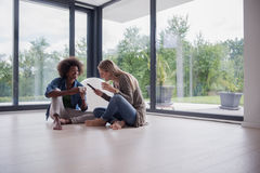 Multiethnic women sit on the floor and drinking coffee Stock Images