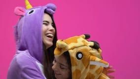 Multiethnic women in unicorn and giraffe pajamas hugging and laughing, fun. Stock footage stock footage