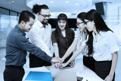Multiethnic workers joining hands together Royalty Free Stock Photo