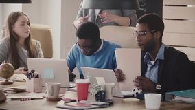 Multiethnic young business people sit by the table and cooperate, work with laptops and talk in modern healthy office.