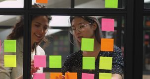Multiethnic young businesswomen managing working process together at kanban board.