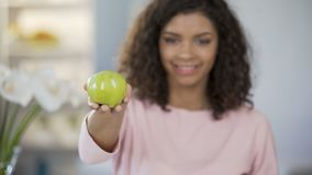 Multiethnic young woman offering apple, smiling at camera, healthy lifestyle