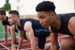 Multiethnische Athletengruppe bereit zu laufen Fokus auf afrikanischem Mann lizenzfreie stockfotos