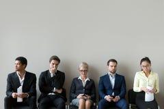 Multiethnische Bewerber, die in der Reihenreihenlinie sich vorbereitet für Interview sitzen lizenzfreie stockbilder