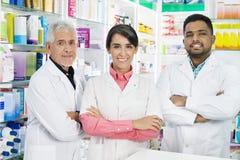 Multiethnische Chemiker, welche die Arme gekreuzt in der Apotheke stehen Stockbilder