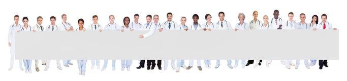 Multiethnische Doktoren, die leere Fahne halten Stockbild