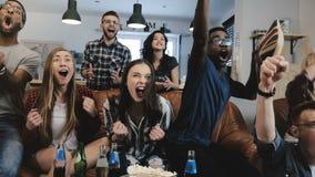 Multiethnische Fans gehen verrückt, Ziel im Fernsehen feiernd Leidenschaftliche Fußballanhänger schreien mit Arme angehobener Zei lizenzfreie stockfotos