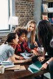 Multiethnische Frauen, die digitale Tablette beim Büro zu Hause bearbeiten betrachten Lizenzfreies Stockfoto