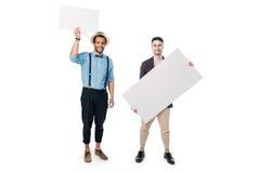 Multiethnische Freunde, die leere Fahnen lokalisiert auf Weiß halten Stockfotos