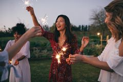 Multiethnische Freunde, die Partei mit Wunderkerzen genießen stockbilder