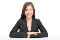 Multiethnische Geschäftsfrau, die am Schreibtischlächeln sitzt Stockfoto