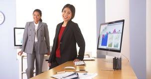 Multiethnische Geschäftsfrau zwei, die im Büro steht stockbild