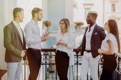Multiethnische Geschäftsleute, die Kaffeepause am Balkon des Bürogebäudes haben lizenzfreie stockfotos