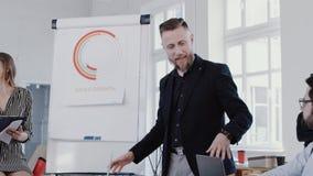 Multiethnische Geschäftsleute hören auf den mittleren gealterten Trainermann, der Verkäufe im modernen Büro, Zeitlupe ROTES EPOS  stock video