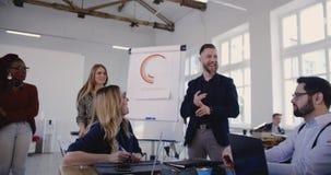 Multiethnische Geschäftsleute hören, klatschen zur glücklichen hübschen Mitte alterten den männlichen Teamleiter, der im modernen stock video