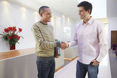 Multiethnische Geschäftsmänner, die Hände im Büro rütteln stockfotografie