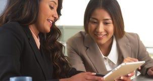 Multiethnische Geschäftsfrauen, die Informationen über Tablette wiederholen Stockfoto