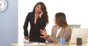 Multiethnische Geschäftsfrauen, die versuchen, ein Abkommen am Telefon zu schließen Stockfoto