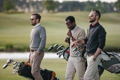 multiethnische Golfspieler, die Taschen mit Golfclubs halten und auf Golf gehen lizenzfreie stockfotografie
