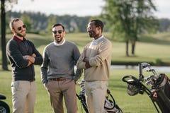 Multiethnische Golfspieler, die zusammen Zeit im Golfplatz verbringen lizenzfreie stockbilder