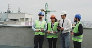 Multiethnische Gruppe des Arbeitskraftingenieur-Architektenvorarbeiters, der den Plan der Baustelle auf der Dachspitze von analys stock footage