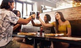Multiethnische Gruppe Freunde, die alkoholfreie Getränke am Café rösten stockbilder