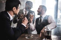 Multiethnische Gruppe Geschäftsmänner, die zuhause Whisky rauchen und trinken lizenzfreies stockfoto